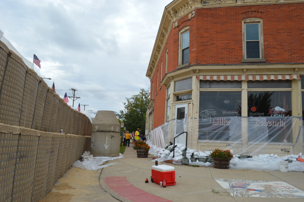 Volunteers work to sandbag the historic Little Bohemia building on Sunday, Sept. 25, 2016, in Cedar Rapids, Iowa. The building is on the dry side of HESCO barriers erected on 16th Avenue SE. (photo/Cindy Hadish)