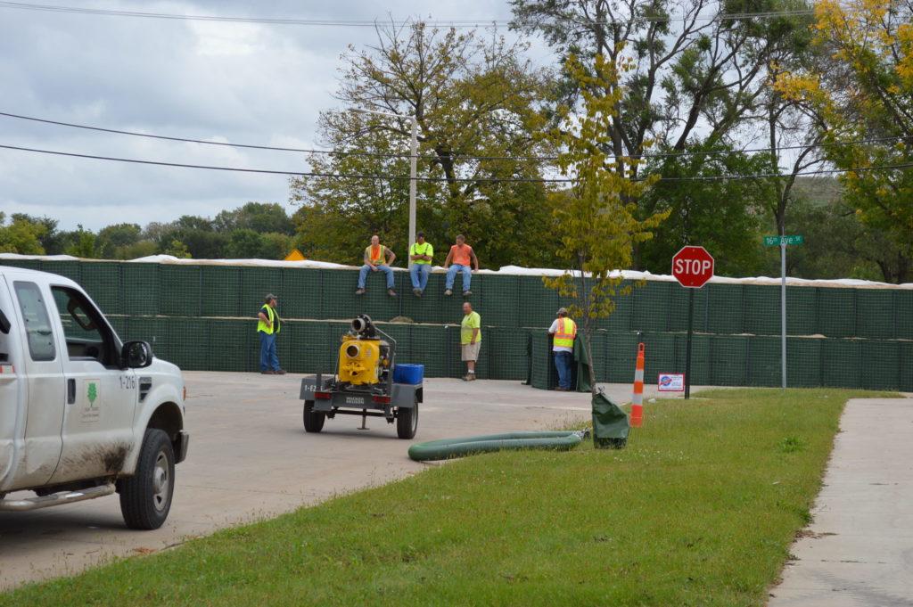 Workers sit on HESCO barriers erected along 16th Avenue SE in Cedar Rapids, Iowa. (photo/Cindy Hadish)